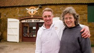 Alan and Jane Hewson Stood outside their barn